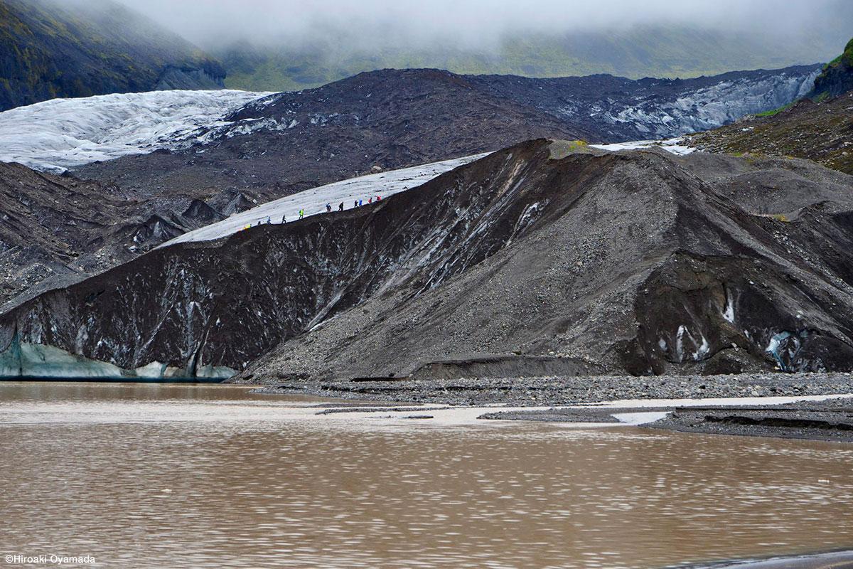 以前は手前の氷河湖も厚い氷河で覆われていた。土砂で黒ずんだ氷河の縁をハイキングする観光客たち ©Hiroaki Oyamada